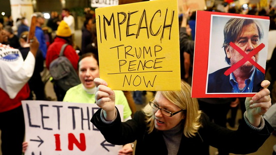 A woman holds signs against Steve Bannon and encouraging the impeachment of Trump and Pence during a protest of Donald Trump's travel ban from Muslim majority countries at the International terminal at Los Angeles International Airport (LAX) in Los Angeles