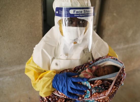 Медицинский работник в специальном защитном костюме несет ребенка, который, вероятнее всего, заражен лихорадкой Эбола