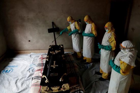 Специалисты дезинфицируют помещение, в котором находится гроб с телом мужчины, предположительно скончавшегося от вируса Эбола.