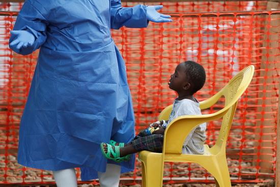 Помогают бороться с вирусом нередко те, кто сам перенес заболевание. На фото — волонтер, переболевший Эболой, играет с ребенком, у которого подозревают лихорадку.