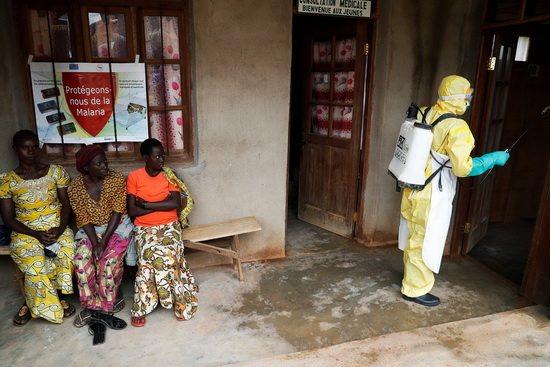 Эти женщины сидят рядом с помещением, в котором умирает маленький ребенок — предположительно от вируса Эбола.