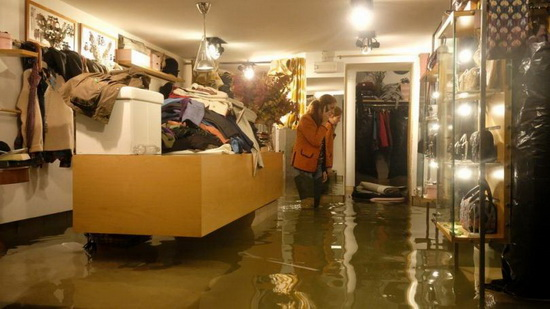 В магазинах работники спасают от воды свои товары. Часть товаров может пострадать от чрезмерной влажности.