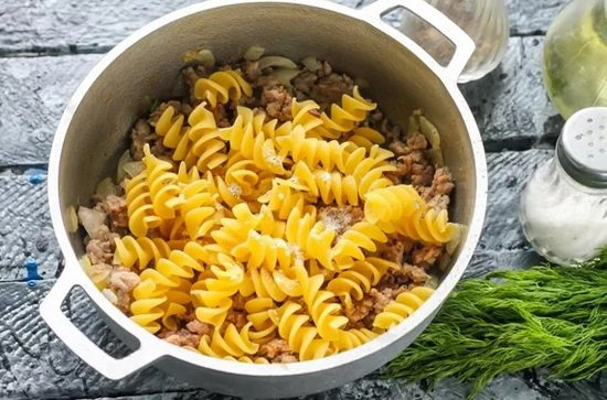 Всыпать выбранный сорт макарон, соль и молотый черный перец по вкусу.