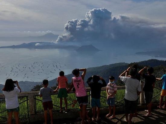 Молодежь, живущая у подножия вулкана Таал, едет на каноэ-аутриггере, а вулкан извергает пепел.