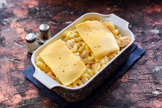 Поверх макарон залить яичную смесь и положить пару ломтиков вкусного твердого сыра.