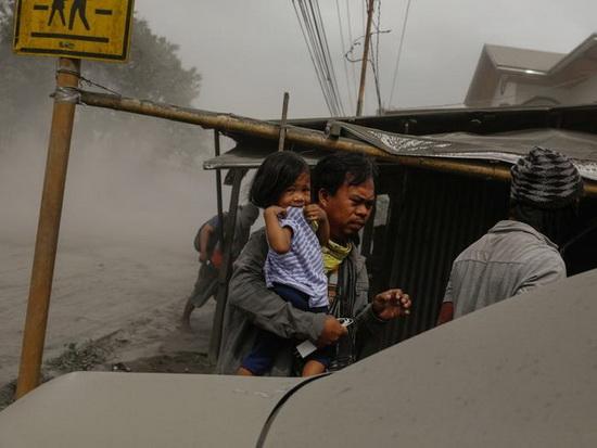 Семья, живущая рядом с извержением вулкана Таал, эвакуируется в Лемери, Батангас, Филиппины, 13 января 2020 года.