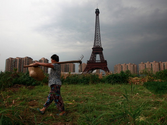 Фермер идёт по грунтовой дороге мимо копии Эйфелевой башни в Ханчжоу